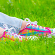 Colored sneakers on the green grass - Stock Photo