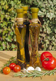 Oil and vinegar bottles in a sunny garden — Stock Photo
