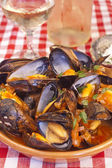 Steamed mussels with marinara sauce and a glass of wine — Stock Photo