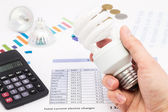 Light bulb whit calculator and euro coins — Stock Photo