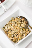 Pumpkin seeds in ceramic bowl on table — Stock fotografie