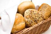 Wicker basket of freshly baked dinner rolls — Stock Photo