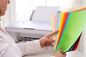Mujer selecciona color de papel para impresora. — Foto de Stock