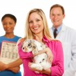 Stock Photo: Veterinarian: Customer Holds Rabbit with Vet Behind