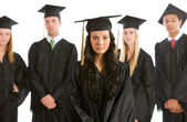Graduation: Serious Graduate with others Behind — Stock Photo
