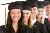Graduation: Female Graduate Leads Line of Students — Stock Photo