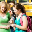 Stock Photo: School Bus: Girl Not Impressed with Friend's Report Card