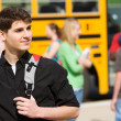 School Bus: Male Student Waiting By Bus - Stock Photo