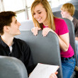 School Bus: Girl Talks to Guy Doing Schoolwork - Stock Photo