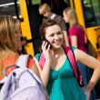 Royalty-Free Stock Photo: School Bus: Girl Calls Friend Before Boarding Bus