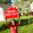Stock Photo: Home: WomHolds Up For Sale Sign