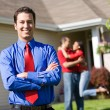 Home: Agent with Excited Couple in Background — Stock Photo #24358251