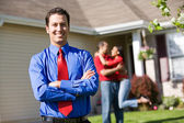 Home: Agent with Excited Couple in Background — Stok fotoğraf