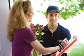 Delivery: Woman Signs for Flowers — Stok fotoğraf