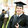 Stock Photo: Graduation: Smart Graduate with Others Behind