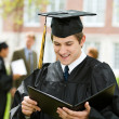 Graduation: Graduate Reads Diploma — Stock Photo