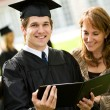 Stock Photo: Graduation: Recent Graduate Stands with Mother