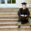 Stock Photo: Graduation: Graduate Sits on School Steps