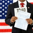 Politician: Holding Up the US Income Tax Form — Stock Photo