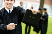 Graduation: Excited Student Points at Diploma — Stock Photo