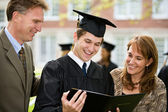 Graduation: Proud Family Admires Diploma — 图库照片