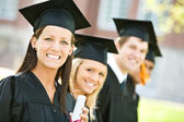 Graduation: Line of Graduates Look to Camera — Stockfoto