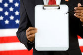 Politician: Pointing to a Blank Paper on a Clipboard — Stock Photo