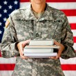 Soldier: Holding Stack of Text Books — Stock Photo #24778785