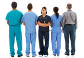 Doctors: Nurse Faces to Camera with Others Turned — Stockfoto