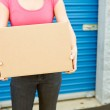 Storage: Woman With Box Stands By Door — Stock Photo