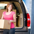 Storage: Woman Lifts Box from Truck — Stock Photo