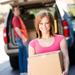 Storage: Woman Carries Box from Truck — Stock Photo