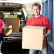 Storage: Man Holding Box with Woman Behind — Stock Photo #25016797