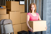 Storage: Woman with Boxes Behind — Stock Photo