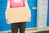 Storage: Woman With Box Stands By Door — 图库照片