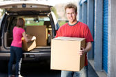 Storage: Man Holding Box with Woman Behind — Stock Photo