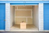 Storage: Woman Peeking To Side Out of Box in Unit — Stock Photo
