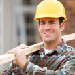 Stock Photo: Construction: Worker Stands with 2x4 on Shoulder