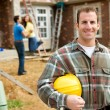 Construction: Contractor with Excited Home Owners in Background - Stock Photo