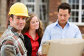 Construction: Contractor with Agents Behind — Stock Photo