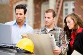 Construction: Group Studies Blueprints and Computer Plans — Stock Photo