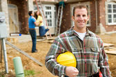 Construction: Contractor with Excited Home Owners in Background — Stock Photo