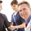 Doctors:  Cheerful Doctor with Patient and Nurse — Stock Photo