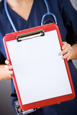 Nurse: Holding Out Blank Clipboard — Stock Photo