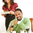 Couple: Man Looking to Camera While Girlfriend Brings Dinner — Stockfoto