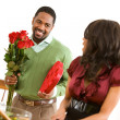 Couple: Man Has Candy and Flowers for Girlfriend — Stockfoto