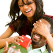 Couple: Woman Surprises Man with Gift — Stockfoto