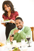Couple: Man Looking to Camera While Girlfriend Brings Dinner — Stock Photo