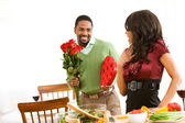 Couple: Man Surprises Woman with Candy and Flowers — Stock Photo