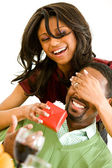 Couple: Woman Surprises Man with Gift — Stock Photo